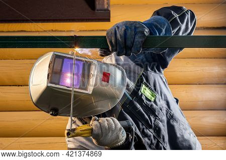 Worker Male Welder At A Construction Site Welds A Metal Structure On A Fence, Welding Process Close-