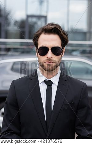 Bearded Bodyguard In Suit And Sunglasses With Security Earpiece Near Modern Car On Blurred Backgroun
