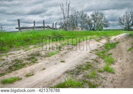 Dirt Road Is Overgrown With Green Grass. Dirt Country Road On A Hill, Against The Background Of Old
