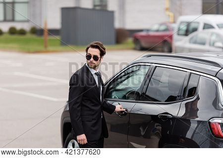 Bodyguard In Suit And Sunglasses With Security Earpiece Opening Door Of Modern Auto.