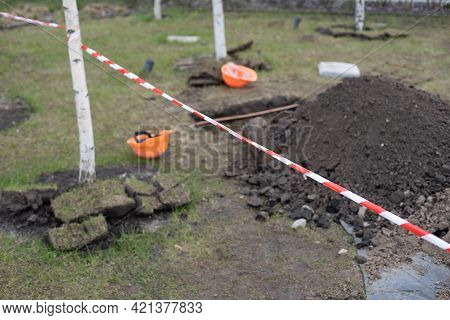 Wooden Spade Resting On The Side Of A Hole Dug Into A Lawn
