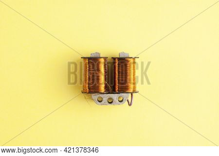An Electricity Transformer With Copper Winding On Yellow Background