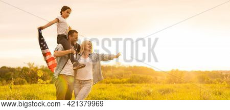 Patriotic Holiday. Happy Family, Parents And Daughters Children Girl With American Flag Outdoors. Us