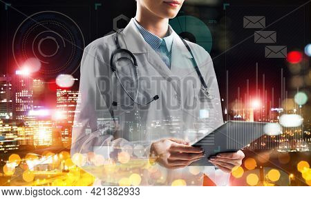 Close Up Of Young Medical Industry Employee Standing Against Night City View And Holding Tablet In H