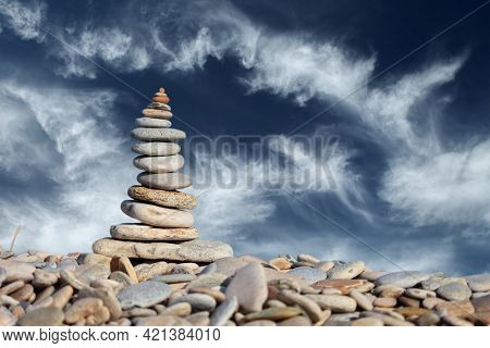 Stack of zen stones on pebble beach against blue sky background