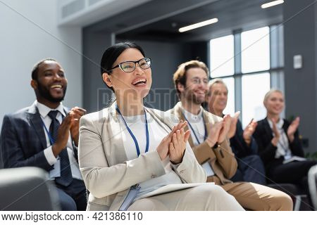 Asian Businesswoman Applauding During Seminar Near Blurred Interracial Colleagues.