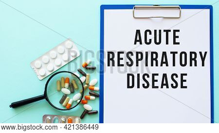 A Clipboard With Paper Lies On A Table Near Drugs. Inscription Acute Respiratory Disease.