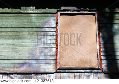 A Dilapidated Wooden Abandoned House. Old Building. Uninhabited House. A Boarded-up Window And No On