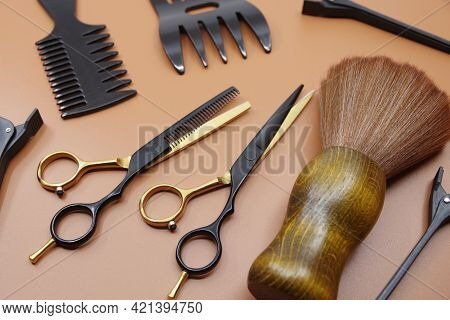 Professional Hairdressers Tools Isolated On Brown Background. Hairdressers Scissor, Comb And Hairpin