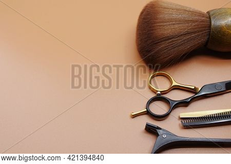 Hairdressers Tools Isolated On Brown Background With Copy Space For Your Text. Hairdressers Scissor