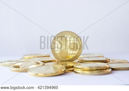 Ripple Coin Stand On Other Cryptocurrencies. Pale Blue Background.