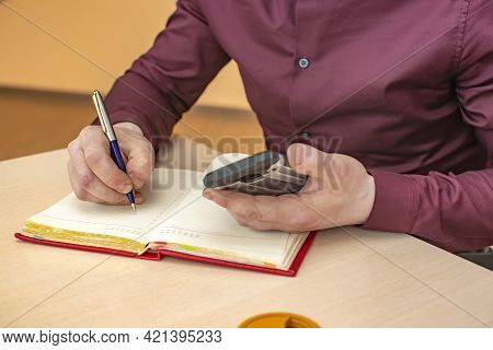 View Of The Hand Of A Business Person With A Writing Pen In An Office Room, Who Writes Notes In A No