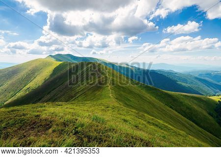 Mountain Landscape In Summer. Grassy Meadows On The Hills Rolling In To The Distant Peak Beneath A S