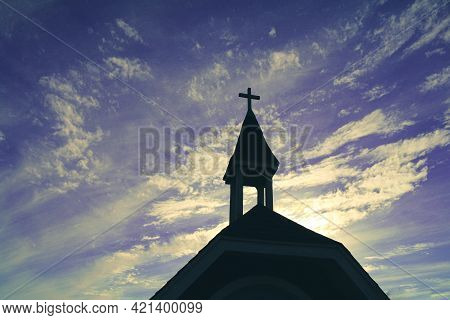 Heavenly Religious Church Chapel Steeple In Silhouette Against A Azure Blue Purple Cloudscape Sky