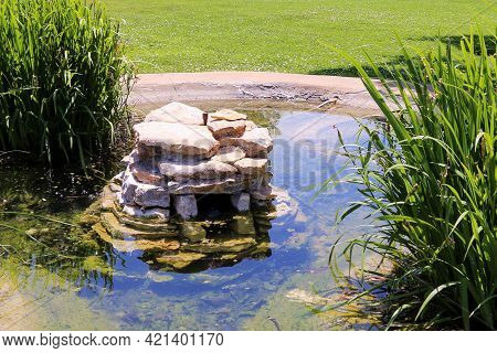 Garden Water Feature Made With Natural Rocks With Lush Lawn And Tall Water Grass