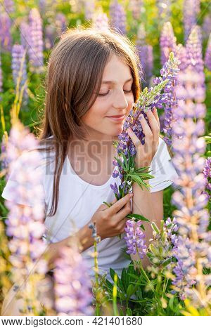 Happy Teenage Girl Smiling Outdoor. Beautiful Young Teen Woman Resting On Summer Field With Blooming