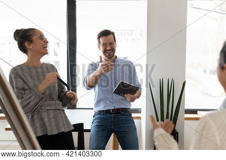 Overjoyed Diverse Colleagues Having Fun At Meeting, Laughing At Joke