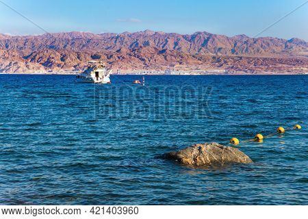 South of Israel. The Gulf of Eilat is a magnificent seaside resort on the Red Sea. Red rocks of the Jordanian coast. Eilat Bay. Red sunny warm day