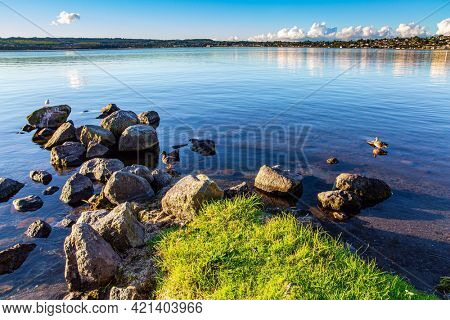 Taupo is the largest lake in New Zealand, North Island.  The most popular holiday destinations for tourists. Quiet evening on the lake. Magnificent sunset.