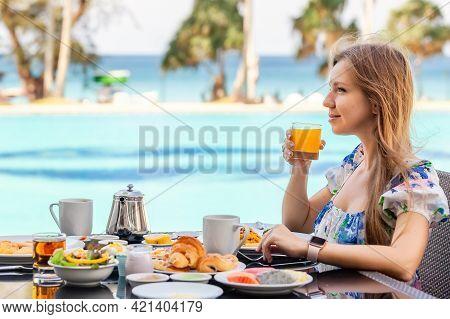 Smiling Woman On American Breakfast Drinking Orange Juice Next To Poolside In Resort. Morning Food N