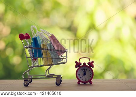 Red Analog Clock With Shopping Cart Or A Supermarket Shopping Basket And Shopping Bag On Wood Table.