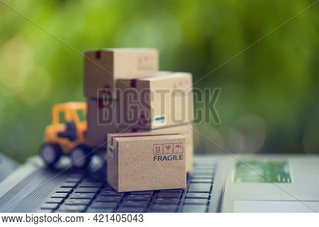 Logistic And Cargo Freight Concept: Fork-lift A Truck Moves A Paper Box On Table. Depicts Internatio