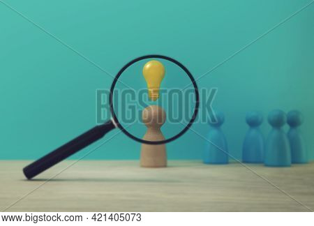 Magnifying Glass With People Model And Light Bulb Icon Outstanding Out From The Crowd. Human Resourc