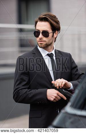 Bearded Bodyguard In Sunglasses Holding Gun Near Blurred Auto.