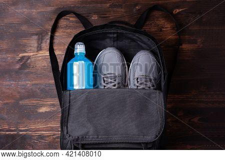 Black Workout Backpack With Sneakers And Blue Isotonic Drink Bottle To Restore Water And Salt Balanc