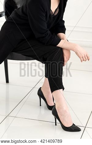 Pretty Young Woman In Black Business Suit And High-heeled Shoes Sits On The Stool , Body Part Close