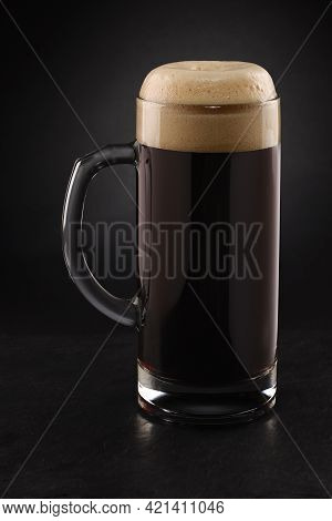 Stein With Fresh Stout Beer With Cap Of Foam On A Black Background.
