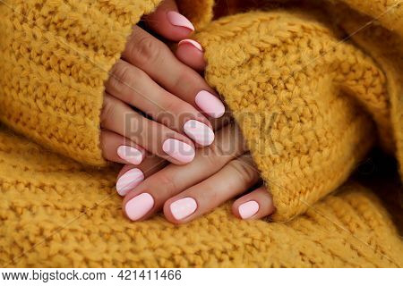 Female Hands With Beautiful Oval-shaped Nails, Matte Pink Manicure Close-up On A Knitted Sweater Bac