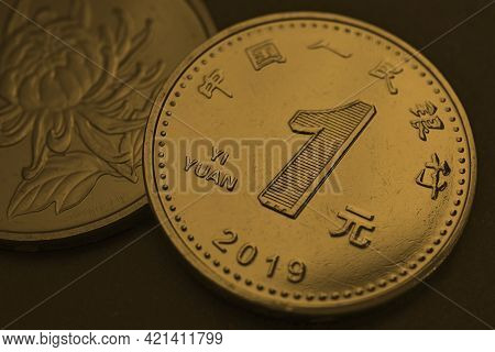 1 One Chinese Yuan Coins Close-up. Dark Yellow-green Or Bronze Tinted Background Or Wallpaper. Econo