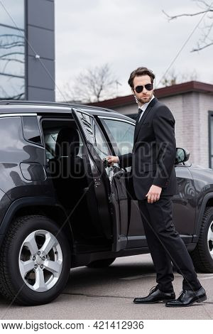 Bearded Bodyguard In Suit And Sunglasses With Security Earpiece Opening Car Door.