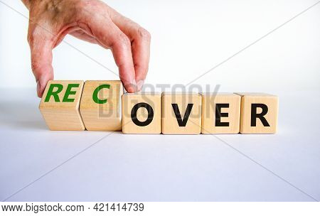 Time To Recover Symbol. Businessman Turns Wooden Cubes And Changes The Word 'over' To 'recover'. Bea