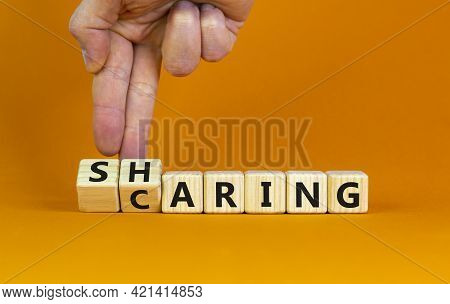 Sharing Is Caring Symbol. Businessman Turns Wooden Cubes And Changes The Word 'sharing' To 'caring'.