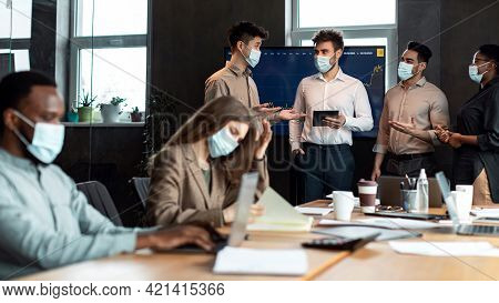 Colleagues In Masks Having Meeting In Boardroom, Working On Project