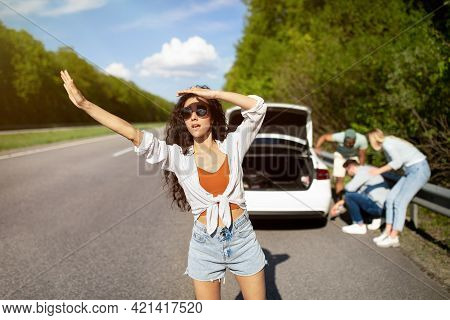Young Woman Trying To Wave Down Car, Asking For Help, Her Friends Trying To Fix Broken Vehicle, Havi