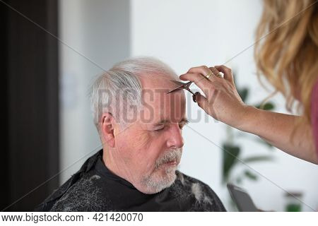 Home Hairdressing Concept, Senior Man The Hair Cutting By Woman Hairdresser