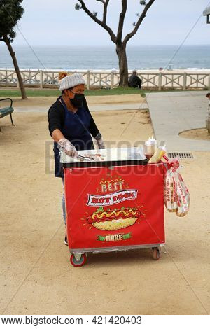 May 14, 2021 Santa Monica California, USA: Hot Dog Push Cart. A street vendor grilling hot dogs with bacon and onions for sale in Santa Monica California. Editorial Use.