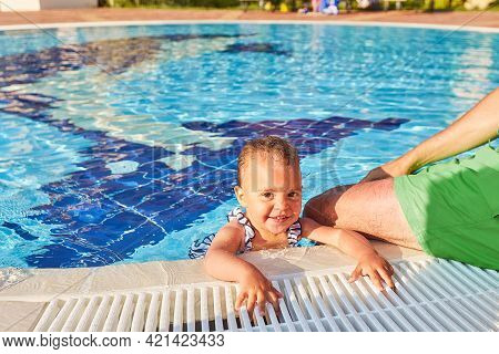 A Girl Takes A Dip In The Pool In The Summer, Looks At The Camera And Smiles.