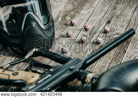 Close Up Of Paintball Gun, Special Balls And Protective Mask, Equipment For Playing Paintball On A W