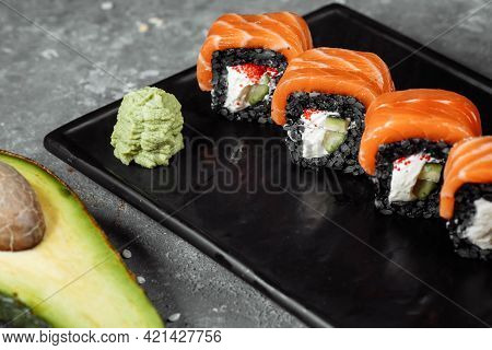 A Set Of Sushi Rolls Philadelphia With Red Fish, Cream Cheese And Black Rise Lies In A Plate Boat. S