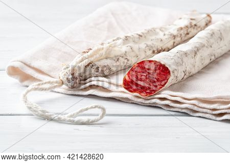 Two Thin Catalan Fuet Sausages On A White Linen Cloth Over A Wooden Table. Close-up Of Traditional S