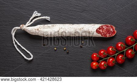 Thin Catalan Fuet Sausage And Bunch Of Red Cherry Tomatoes On A Black Slate Surface. Wide Image Of T