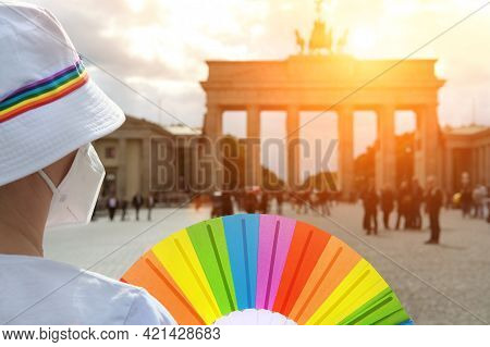 Mature Caucasian Lgbt Woman In Berlin With Rainbow Fan And Ribbon On White Summer Hat. Rainbow, Symb