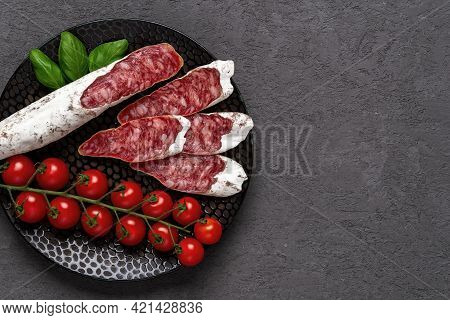 Sliced Thin Catalan Fuet Sausage And Bunch Of Red Cherry Tomatoes On A Black Plate Over Dark Rough S