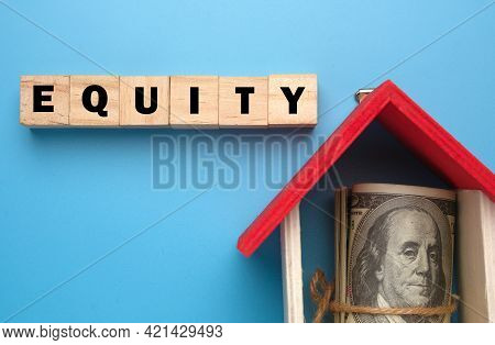 A Picture Of Wooden Block With Equity Word, House Miniature And Fake Money Insight. Equity Is The Di
