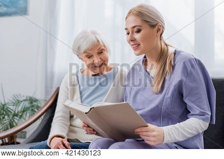 Smiling Nurse Reading Book To Happy Senior Woman On Couch At Home.