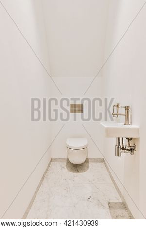 Narrow Lavatory Room With White Walls And Marble Floor And With Wall Hung Hung Toilet And Small Sink
